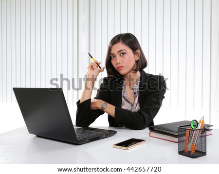 Portrait of young Asian female manager at her workplace, looking at camera with serious expression - stock photo