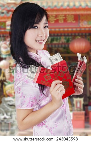Portrait of young asian girl wearing traditional cheongsam clothes and holding dollar cash in envelope at the temple - stock photo