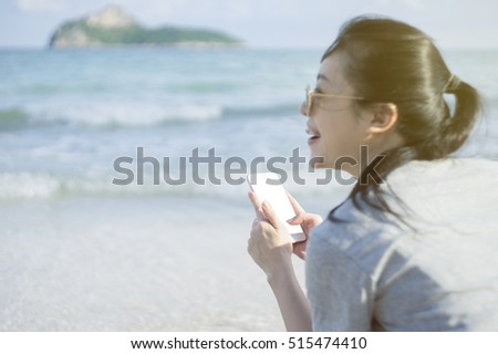 portrait of young asian happy woman using smart phone at beach.technology concept.blurred beach sea background.clipping path included.light effect added.