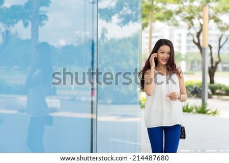 Portrait of young Asian lady calling on the phone - stock photo