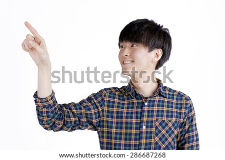 Portrait of young asian man pointing with his finger on white background