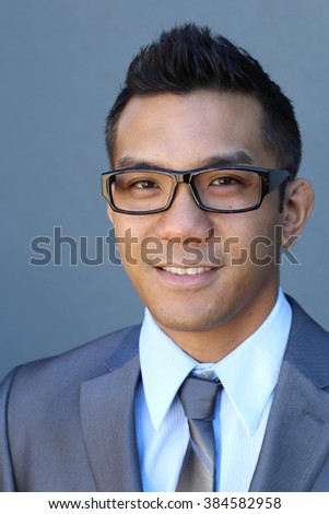 Portrait of young Asian man with glasses in office smiling - stock photo