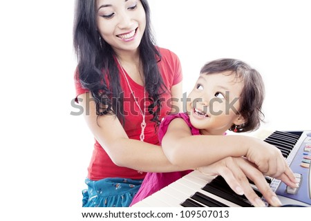 Portrait of young asian mother with her daughter pressing a button on the piano