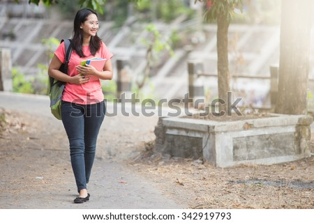 portrait of Young Asian student outdoor walking while holding her book