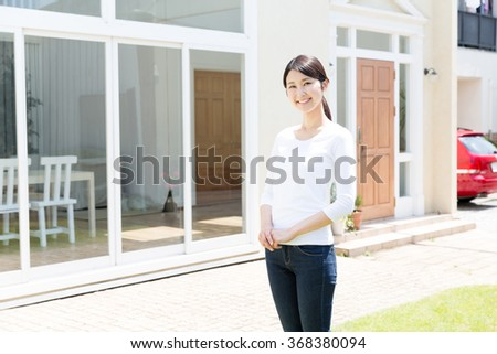 portrait of young asian woman front ob house - stock photo