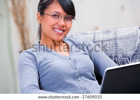 Portrait of young Asian woman smiling to the camera. Sitting on sofa with her laptop at home. - stock photo