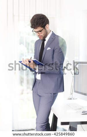 Portrait of young assistant businessman doing some paperwork while standing at his workplace at bank.  - stock photo