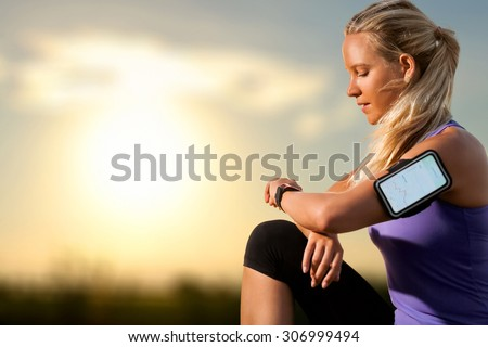 Portrait of young athlete checking workout on smart watch at sunset.Woman wearing armband with smart watch and graphic showing workout results. - stock photo