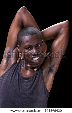 Portrait of young athletic black man with arms tangled behind head as he grabs his neck displaying anxiety and unrest on black background