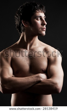 portrait of young athletic man against dark background - stock photo