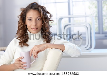 Portrait of young attractive afro woman drinking tea at home.