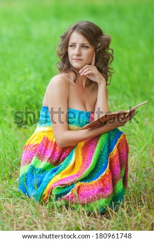 Portrait of young attractive beautiful dark-haired curly woman wearing orange sweater and holding book at summer green park. - stock photo