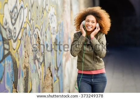 Portrait of young attractive black girl in urban background listening to the music with headphones. Woman wearing leather jacket and blue jeans with afro hairstyle - stock photo
