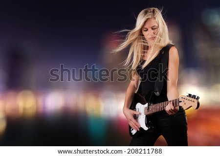 Portrait of young attractive blond woman playing on electric guitar - stock photo