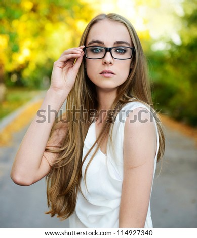 Portrait of young attractive blonde woman wearing eyeglasses and white blouse at summer green park - stock photo