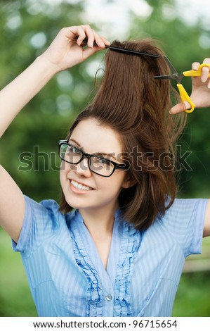 Portrait of young attractive brunette woman cutting her hair at summer green park - stock photo