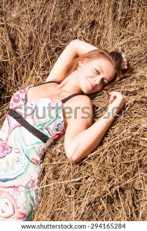 Portrait of young attractive brunette woman standing near hay stack - stock photo