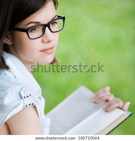 Portrait of young attractive brunette woman wearing glasses, reading book, sitting at summer green park - stock photo