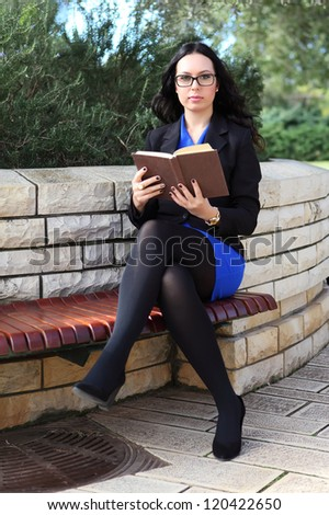 Portrait of young attractive brunette woman with glasses holding a old book