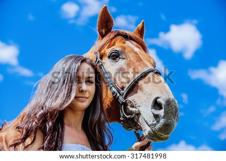 Portrait of young attractive brunette woman with horse against the blue sky.