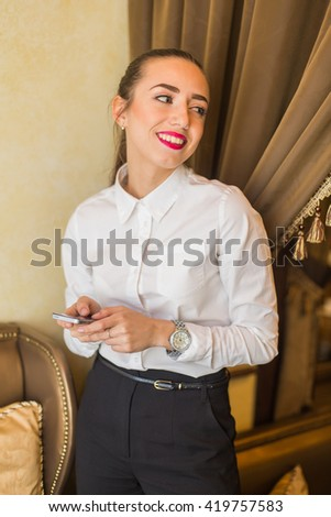 Portrait of young attractive business woman talking on a cell phone in a restaurant.