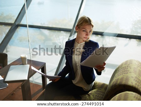 Portrait of young attractive businesswoman examining paperwork in bight light office interior sitting next to the window, business woman read some documents before meeting, filtered image - stock photo