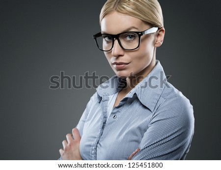 Portrait of young attractive businesswoman wearing glasses isolated on gray background with copy space