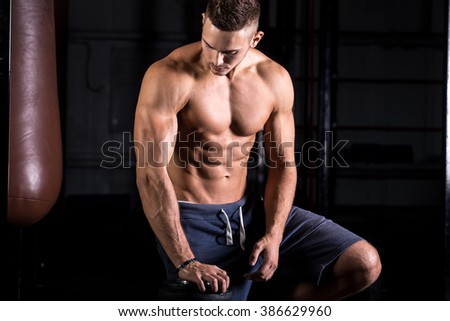 Portrait of young attractive caucasian athletic man working out in gym, leaning on dumbbell, showing upper body muscles - stock photo