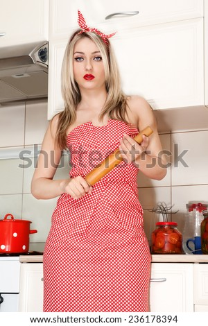 Portrait of young attractive caucasian blonde angry housewife with rolling pin at kitchen. Beautiful young housewife in the kitchen. Woman in pin up style.  - stock photo