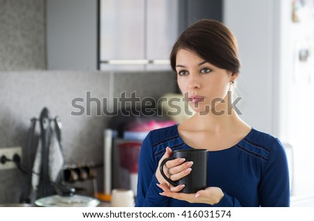 Portrait of young attractive caucasian brunette housewife at kitchen. Morning with cup of coffee.