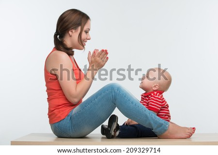 Portrait of young attractive Caucasian mother sitting face to face to her cute toddler son playing clapping hands, lifestyle fun concept, isolated on white - stock photo