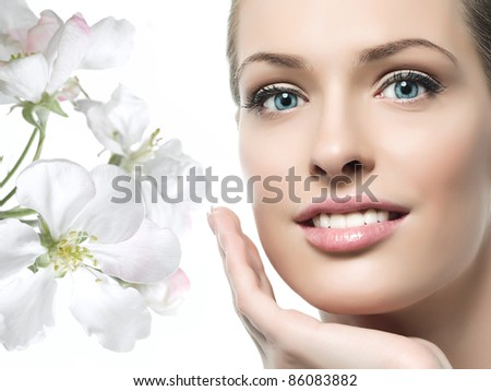 portrait of young attractive caucasian woman toothy smiling looking at camera with spring flowers - stock photo