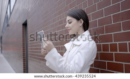 portrait of young attractive caucasian women looking at tablet computer screen in the city. urban people lifestyle background - stock photo
