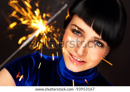 Portrait of young attractive celebrating woman holding sparkles - stock photo