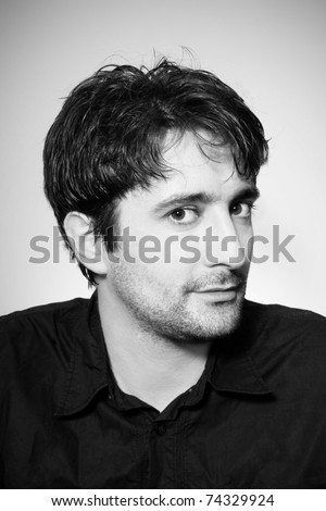 Portrait of young attractive dark-haired smiling man, studio shot