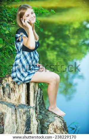 Portrait of young attractive dark-haired woman wearing black dress, speaking on mobile phone, sitting on stump against lake at summer green park. - stock photo