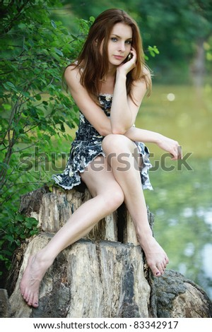 Portrait of young attractive dark-haired woman wearing black dress, speaking on mobile phone, sitting on stump against lake at summer green park.