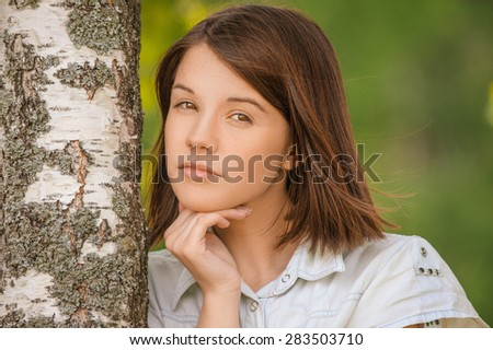 Portrait of young attractive dark-haired woman wearing white chemise embracing birch tree at summer green park. - stock photo