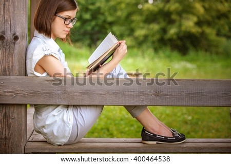 Portrait of young attractive earnest brunette woman wearing white clothes, reading book, sitting at summer green park. - stock photo