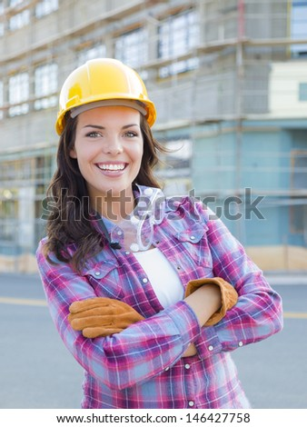 Portrait of Young Attractive Female Construction Worker Wearing Gloves, Hard Hat and Protective Goggles at Construction Site. - stock photo
