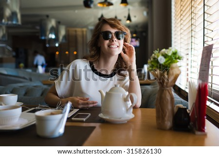 Portrait of young attractive female sitting in a restaurant enjoying breakfast and her leisure time at weekend, gorgeous female smiling charmingly while spending her recreation in the restaurant - stock photo