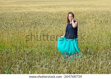 Portrait of young attractive female standing in field  - stock photo