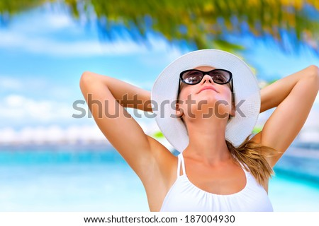 Portrait of young attractive female with hands behind head taking sunbath on the beach, summer vacation on Maldives