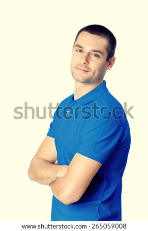 Portrait of young attractive handsome man in blue casual t-shirt clothing, with crossed arms, looking at camera - stock photo
