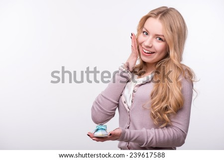 Portrait of young attractive happy Caucasian woman with long fair hair holding cute baby shoe on her palm and melting with joy, isolated on white background, baby expectation concept - stock photo