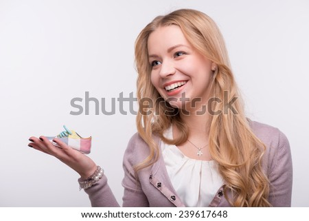 Portrait of young attractive happy Caucasian woman with long fair hair laughing and holding cute baby shoe on her palm, isolated on white background, baby expectation concept - stock photo
