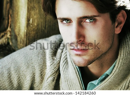 portrait of young attractive man sitting near window - stock photo