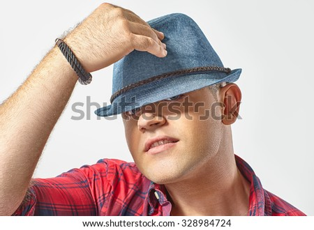 Portrait of young attractive man wearing a hat - stock photo