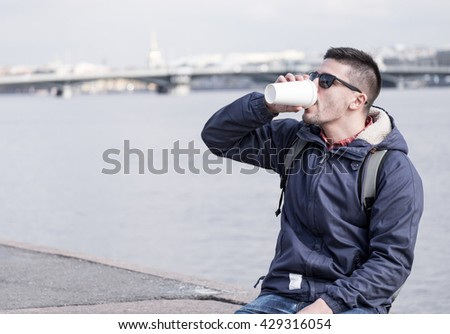 Portrait of young attractive man with coffee cup sitting on promenade and city sight seeings as background - stock photo