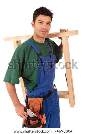 Portrait of young attractive Nepalese carpenter wearing a blue overall, tool belt and a workbench on shoulder . Studio shot. White background. - stock photo